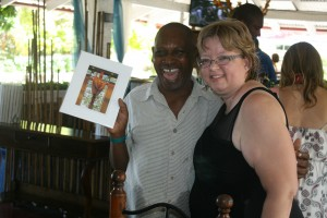 Tanya with Jean Baptiste and her retirement gift (a picture of the cross from OLOL)